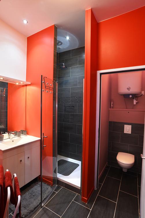 Salle de bains avec carrelage noir et peinture rouge